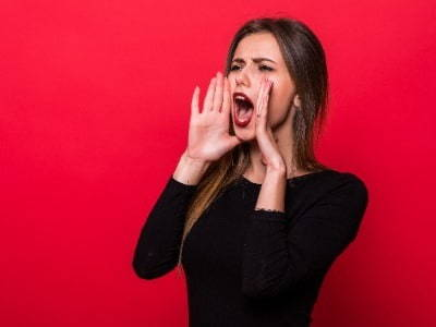 Lady against red wall holding hand up to mouth and shouting